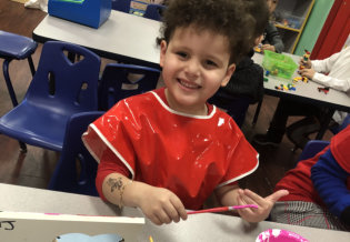 little boy smiling while coloring