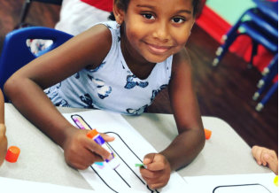 little girl smiling while coloring